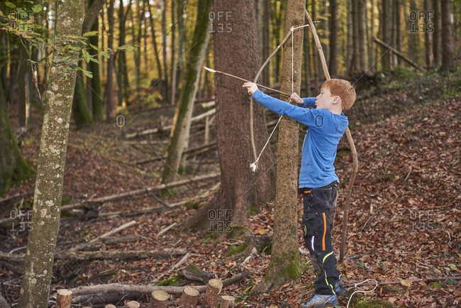Boy aiming with bow in the woods