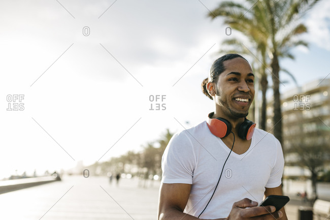 Spain- portrait of smiling young man with headphones and cell phone on beach promenade