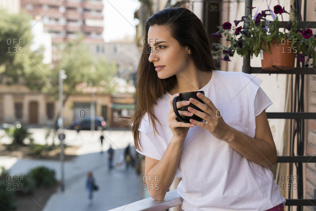 Woman with coffee mug standing on balcony looking at distance