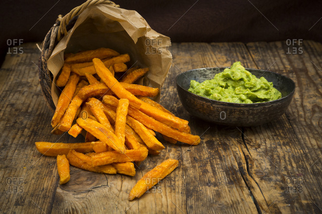 Sweet potato fries and avocado dip on wood