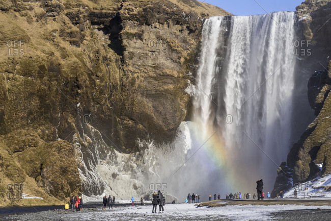 Iceland- people at Skogafoss waterfall with rainbow in winter