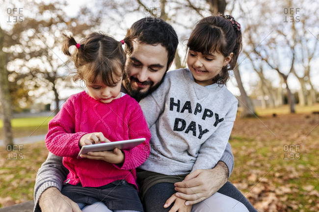 Father with his little daughters looking at tablet in autumnal park