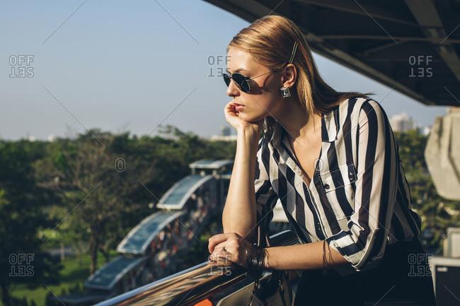 Stylish young woman enjoying sunlight on terrace