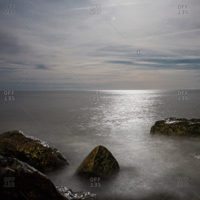 Moonlight glistening on water and rocks along the Connecticut coastline