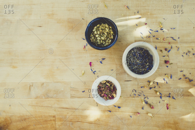 Scattered flower petals and bowls of ingredients for soap making