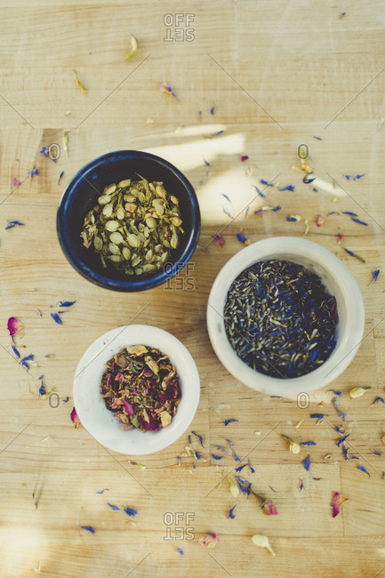 Ingredients in bowls and scattered flower petals for soap making