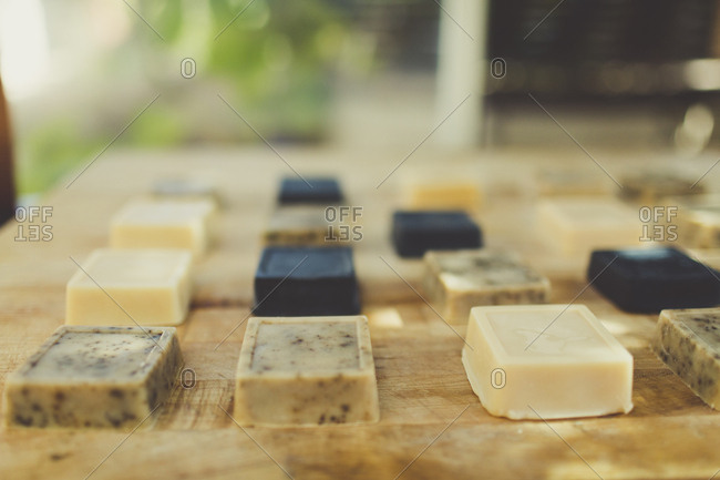 Bars of handmade artisanal soaps on a wooden surface