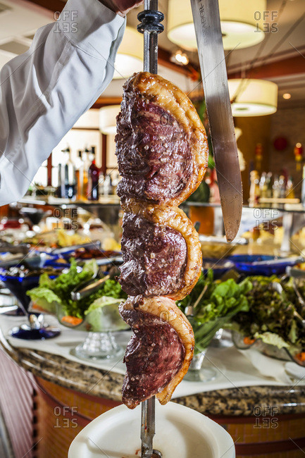 Brazil - December 20, 2008: Chef holding a long skewer of roasted picanha beef