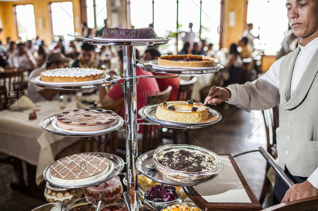 Brazil - December 20, 2008: Dessert cart with many trays of whole custard cakes and person cutting a slice in one of them