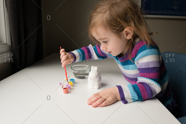 Girl dipping paintbrush in container on table with white Easter bunny