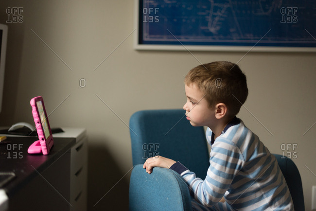 Boy in chair watching digital tablet