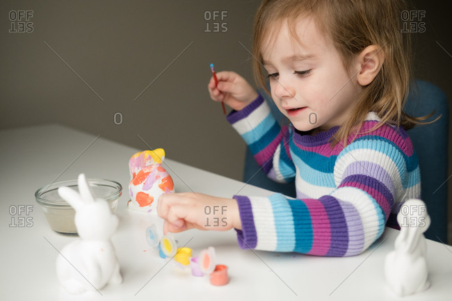 Little girl painting Easter bunnies