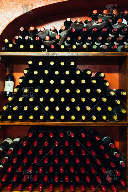 Tuscany, Italy - April 17, 2015: Wine bottles stacked on wooden shelves