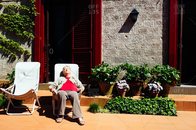 Piano di Sorrento, Italy - April 21, 2015: Senior woman taking a nap in a chair in a courtyard