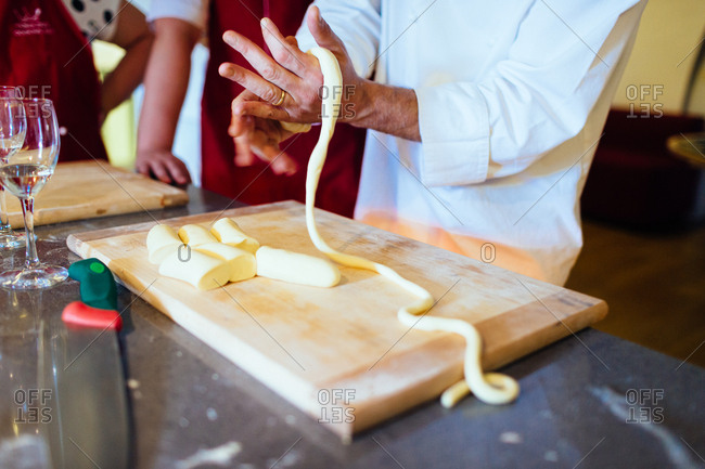 Hands of a chef showing how to make pasta in a kitchen