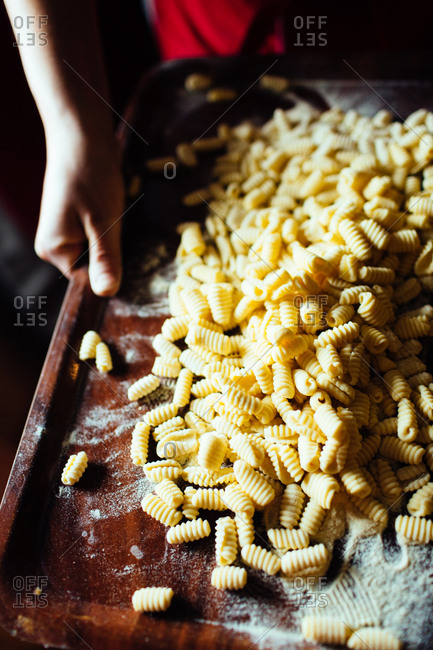 Person holding a wooden tray with fresh spiral pasta