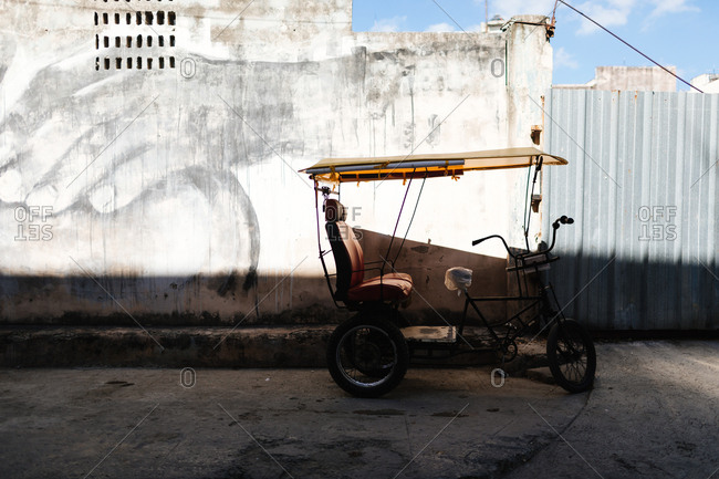 Havana, Cuba - January 24, 2017: Pedicab parked in a street beside a building