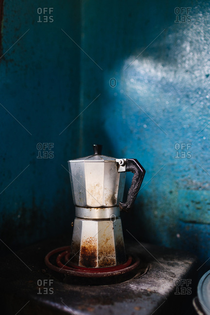 Stained metal coffee kettle on a table in a home with blue walls