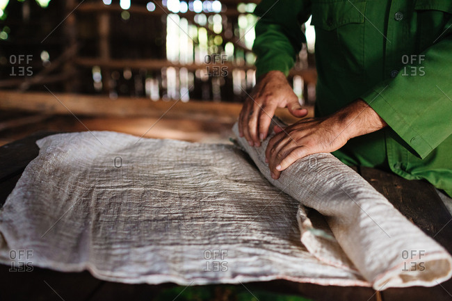 Man rolling tobacco between layers of cloth in an old barn at a cigar farm in Vinales, Cuba