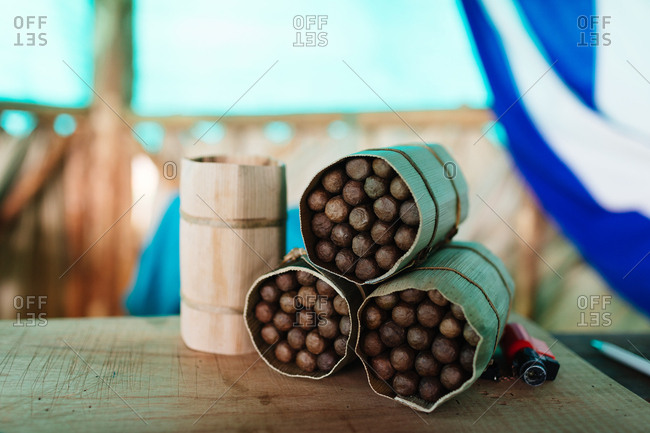 Three bundles of hand rolled cigars wrapped in cloth on a table