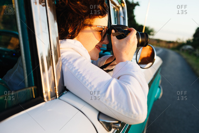 Vinales, Cuba - January 24, 2017: Woman taking a photo from the passenger seat of a classic car