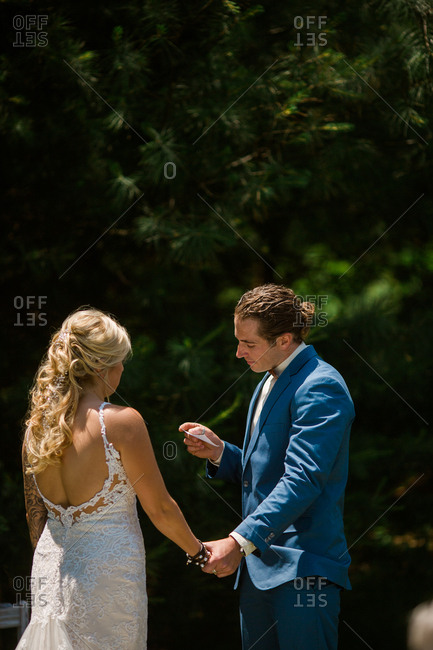 Groom reading his vows to bride during wedding ceremony