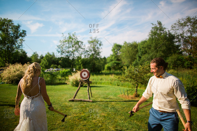 Couple throwing axes at target on wedding day