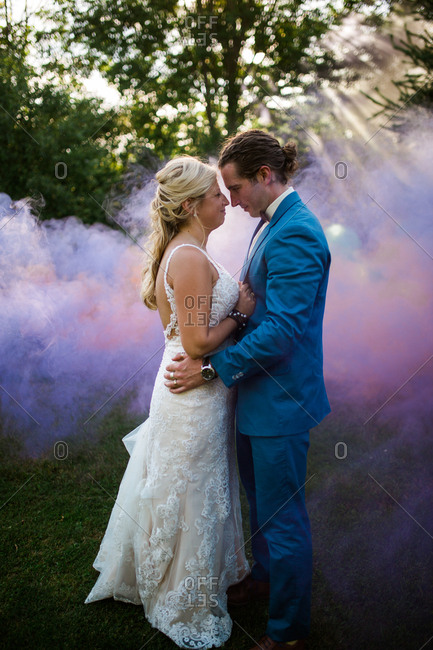 Bride and groom gazing thoughtfully at one another by colorful smoke