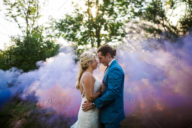 Groom and bride staring thoughtfully at one another by colorful smoke
