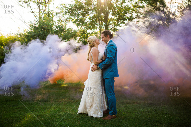 Bride and groom embraced by colorful smoke on their wedding day
