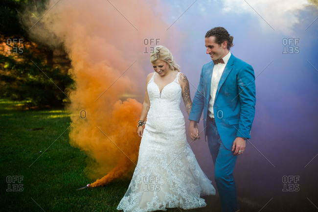 Happy newlywed couple holding hands by colorful smoke