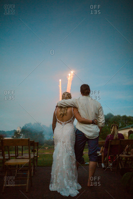 Bride and groom embraced watching fireworks