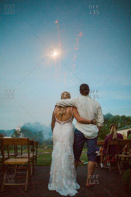 Groom and bride embraced watching fireworks