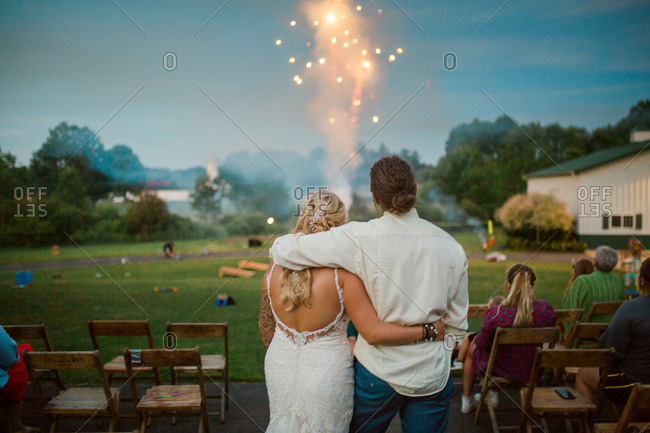 Rear view of bride and groom embraced watching fireworks