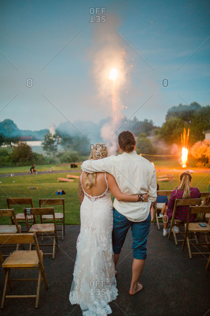 Rear view of groom and bride embraced watching fireworks