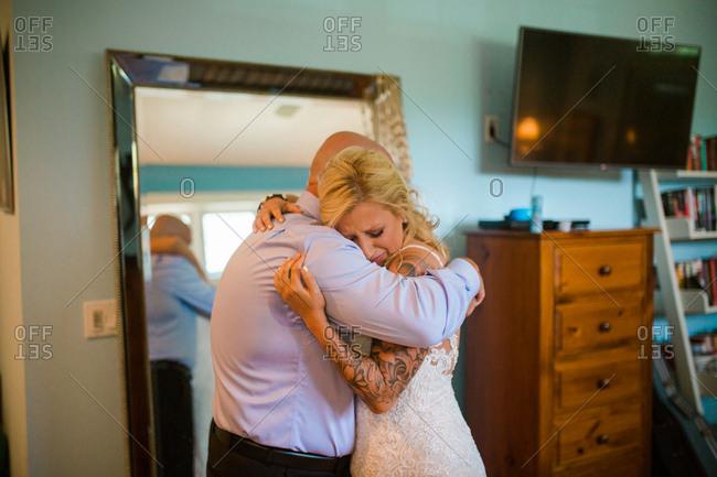 Emotional bride hugging dad on her wedding