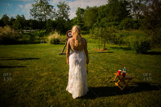 Bride throwing axes at target on wedding day