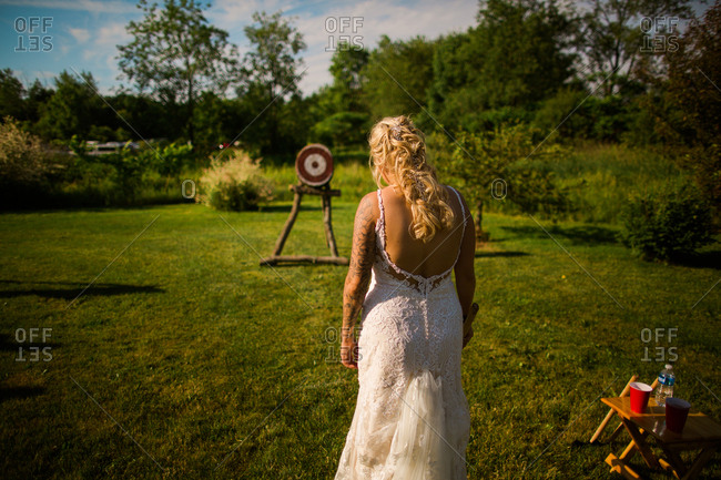 Bride playing axe game on wedding day