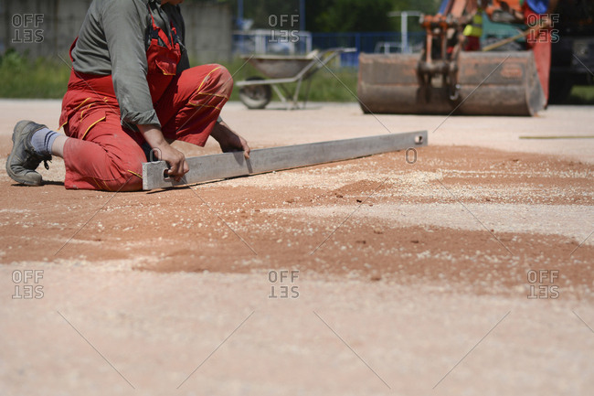 A laborer working spreading gravel and aggregate on a road surface, and a roller in the background