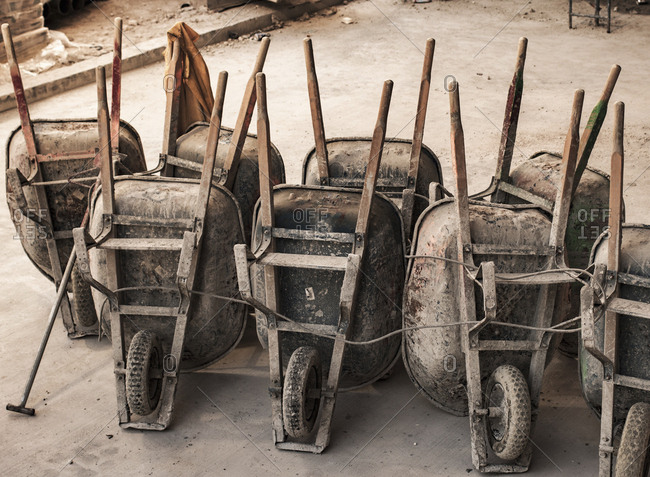 A row of well used old wheelbarrows, propped up at the end of the working day