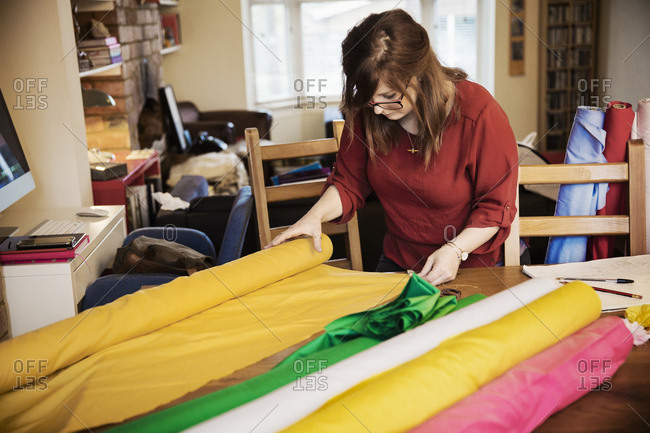 A woman choosing fabric from bolts of bright colored material on a tabletop in a workroom