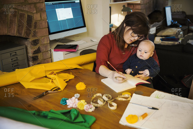 A woman seated with her baby on her lap writing in a notebook Craft material and tools Tabletop in a workroom