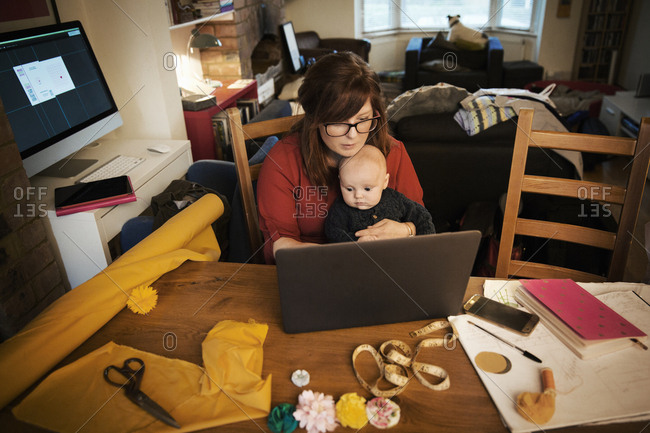 A woman seated with her baby on her lap, multitasking and using a laptop