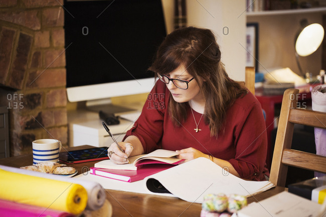 A woman seated at a table making notes, writing in a notebook