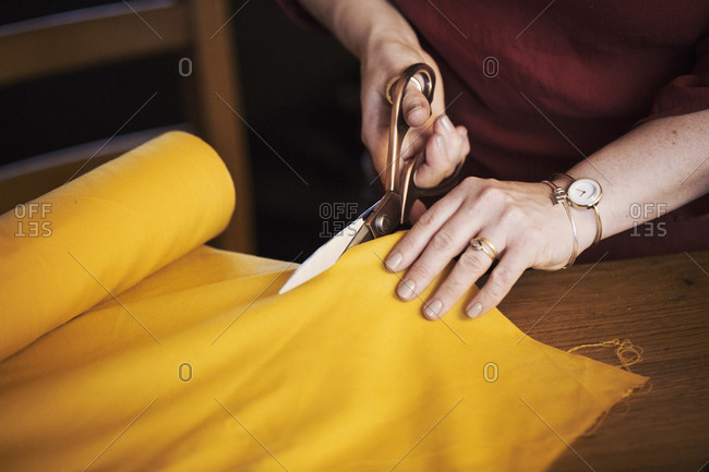 A woman seated at a table using dressmaking scissors to cut yellow material