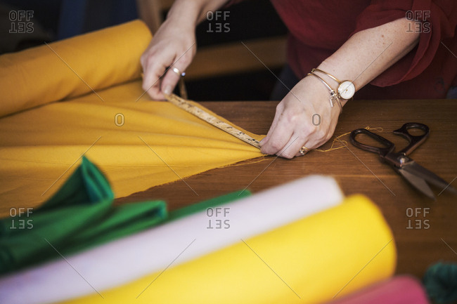 A woman using a tape measure to measure yellow fabric for cutting out