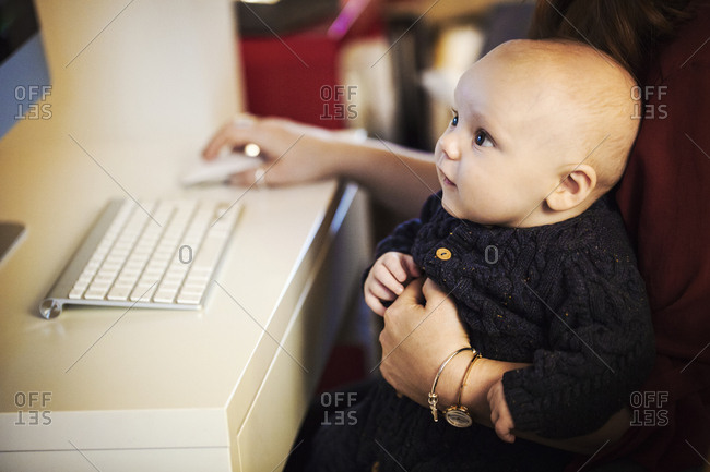 A baby seated on an adult's knee, looking at a computer screen,