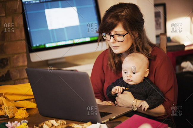A woman seated with a baby on her lap, using a computer laptop, both people looking intently at the screen