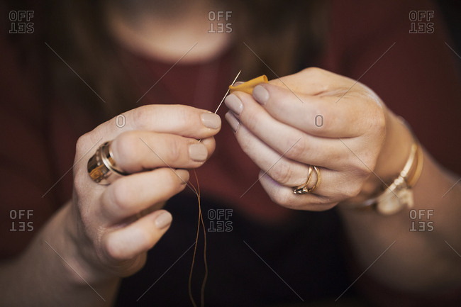 A woman using a needle threaded with cotton thread