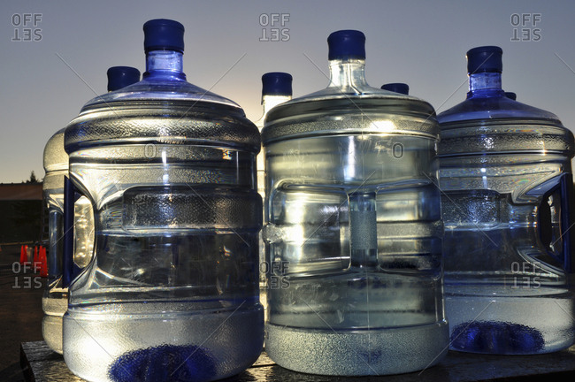 Large bottles of water for water coolers on a table outside